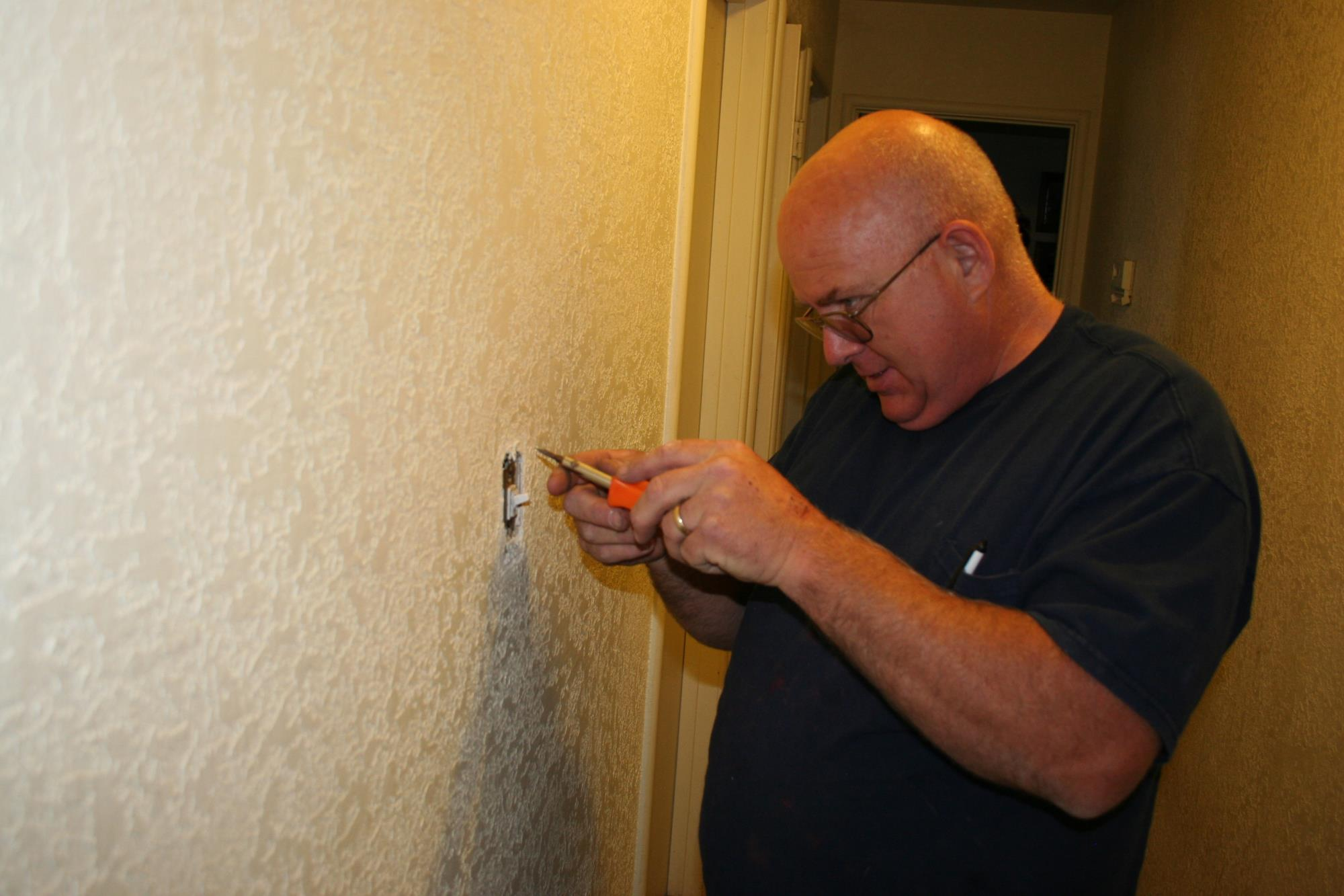 Image of man installing a new light switch in hallway