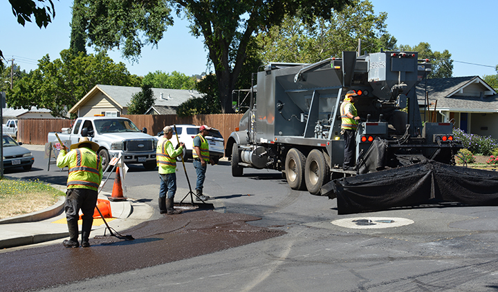 Workers spread a coating of slurry seal to a street in Vacaville.
